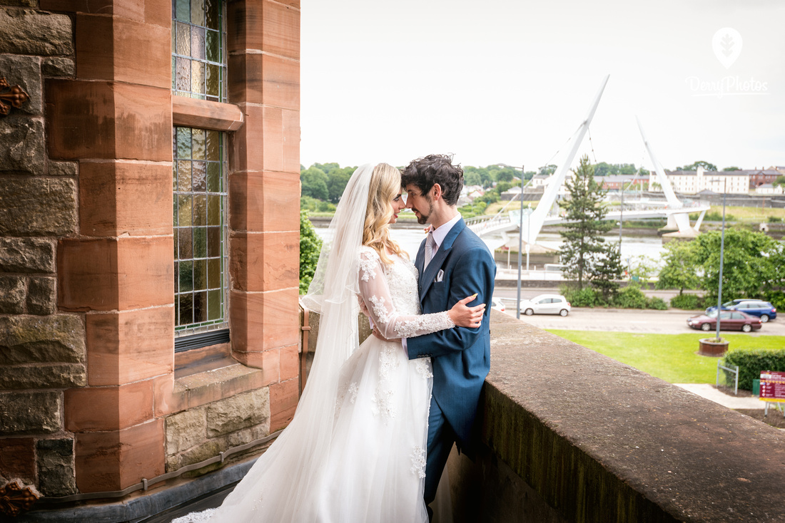 Emmette Dillon & Olivia Doherty Wearing dresses by the Bridal Showroom Suit by The Black Tie Showroom at the Guildhall Derry Wedding venue. Peace Bridge Background