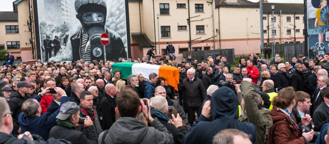 Pictures of Martin McGuinness' Funeral - Martin McGuinness Funeral - Coffin draped in Irish flag passing the bloody sunday Mural in the Bogside Derry